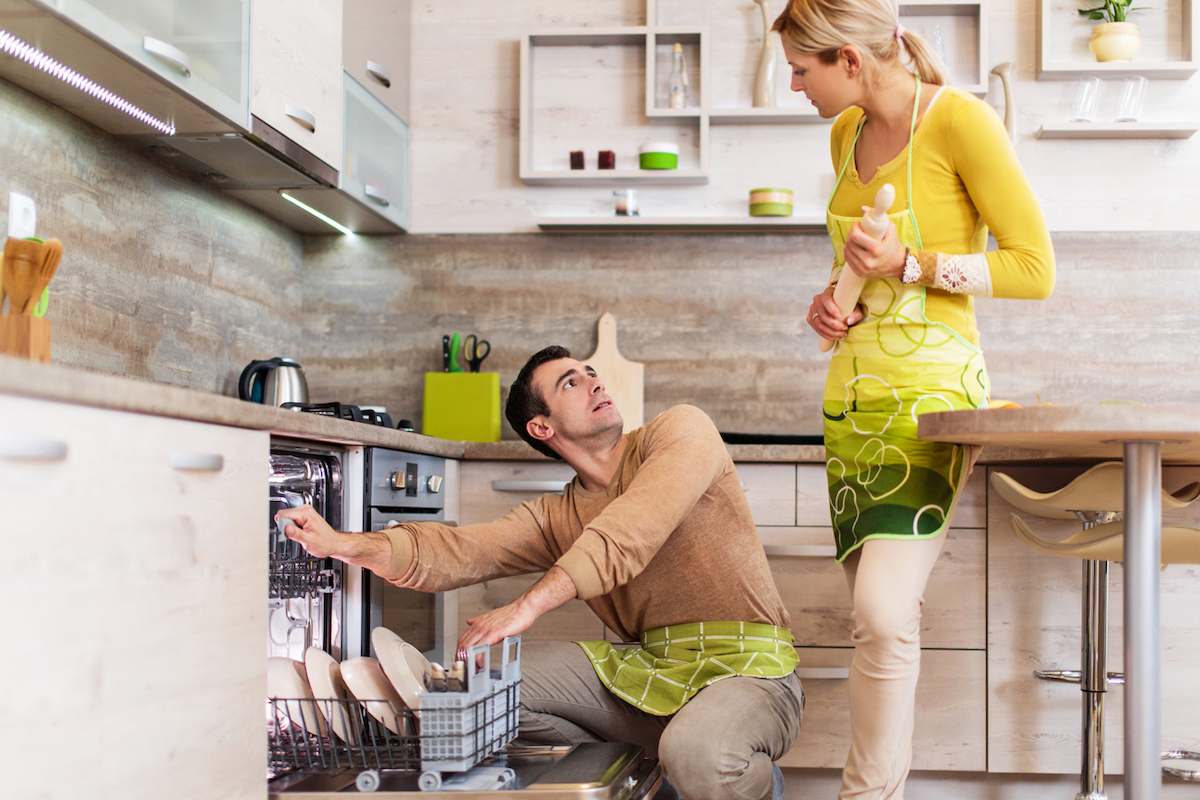 Couple having problems and arguing in the kitchen over dishwasher
