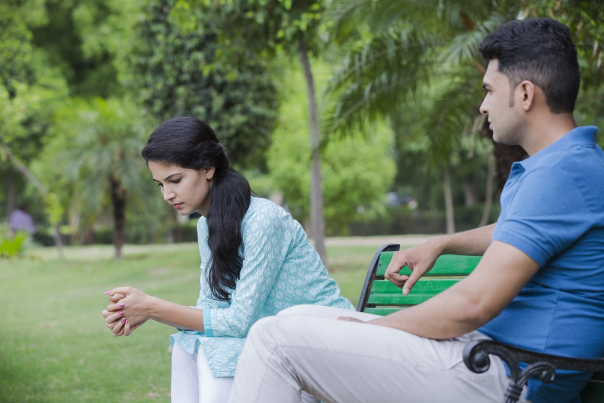 dating couple arguing in silence on a park bench