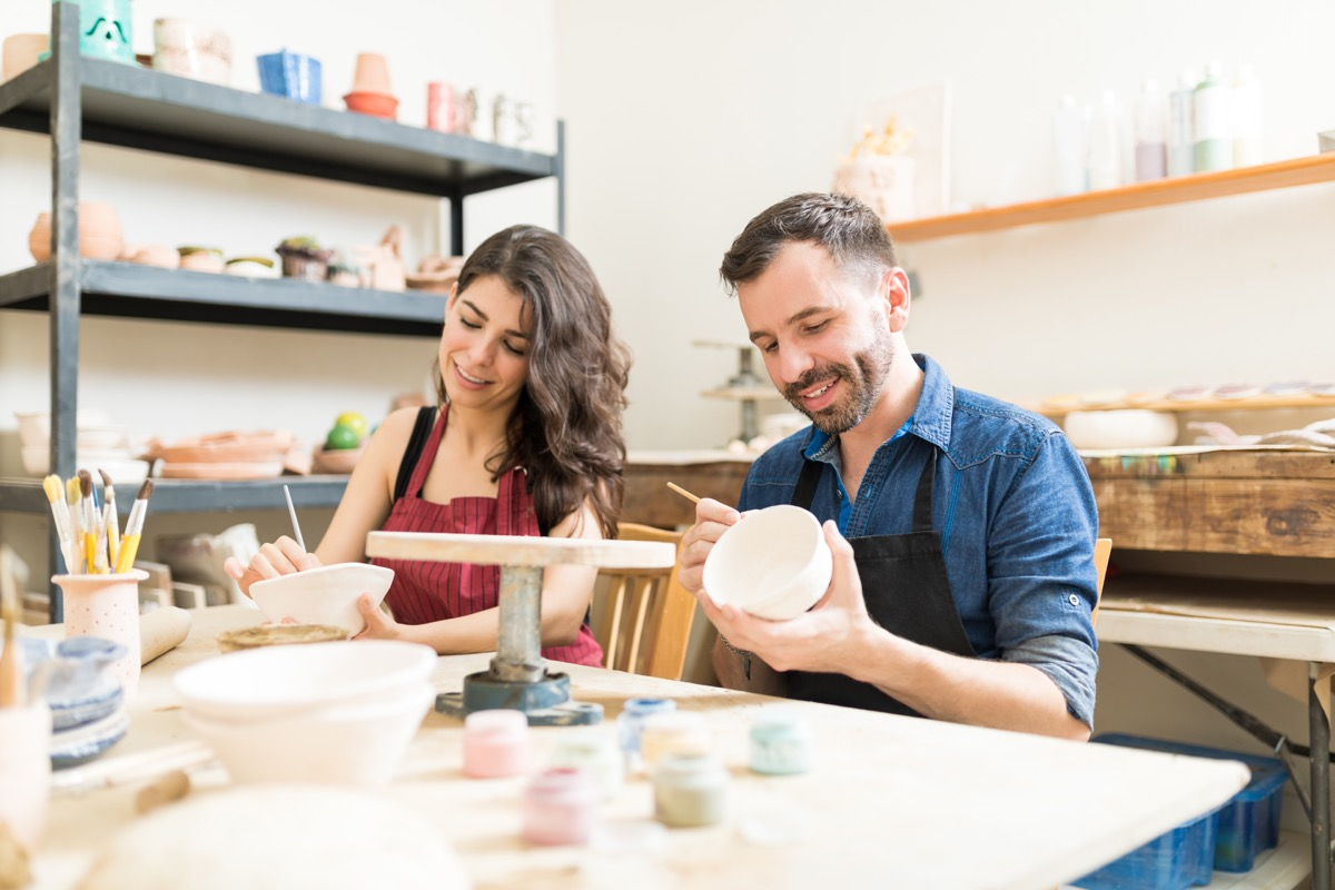 Couple taking an art class painting clay bowls