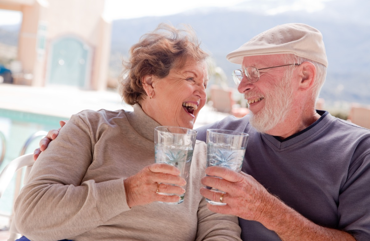 Happy older couple drinking water together