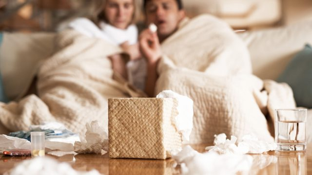 couple suffering with flu while sitting wrapped in blankets on the sofa at home, throwing tissues on coffee table