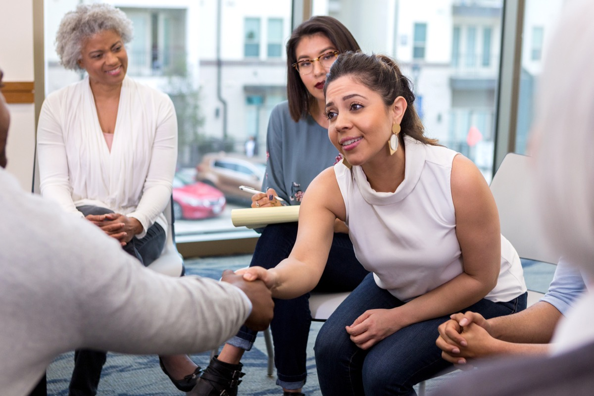 businesswoman sits with colleagues and reaches forward to shake hands with an unseen new client