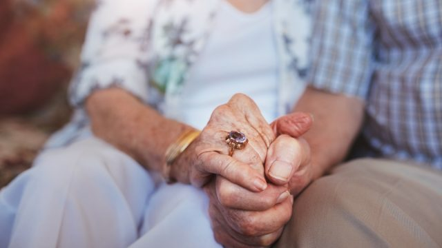 cropped shot of elderly couple holding hands
