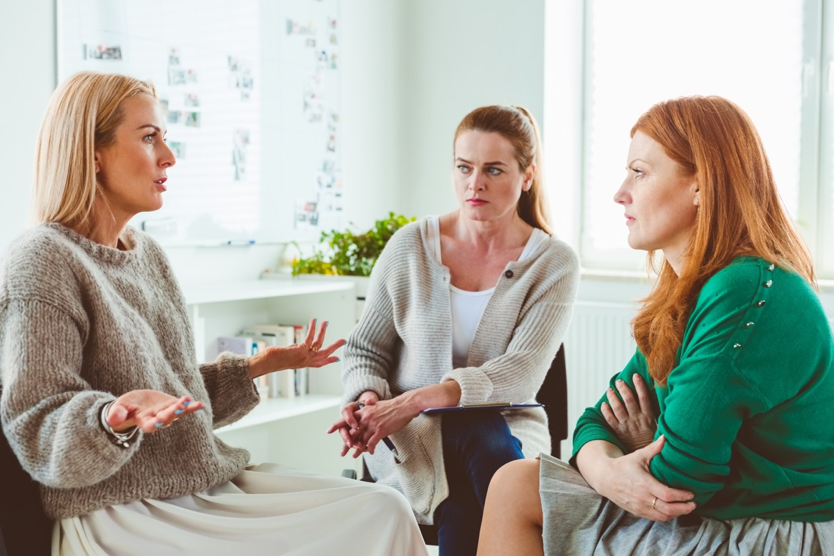 Mature female discussing problems during group therapy. Therapist is sitting with women in session. They are in wellness center.