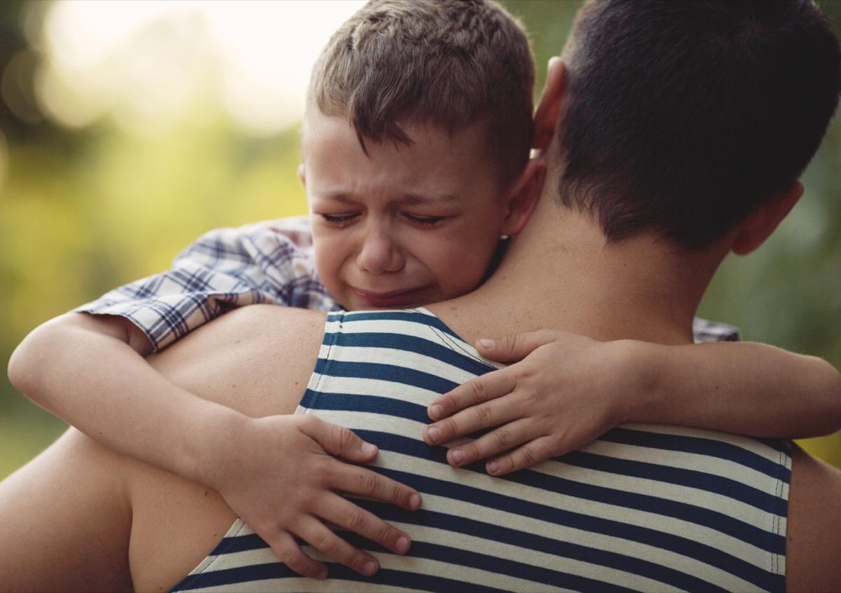 crying boy hugging dad