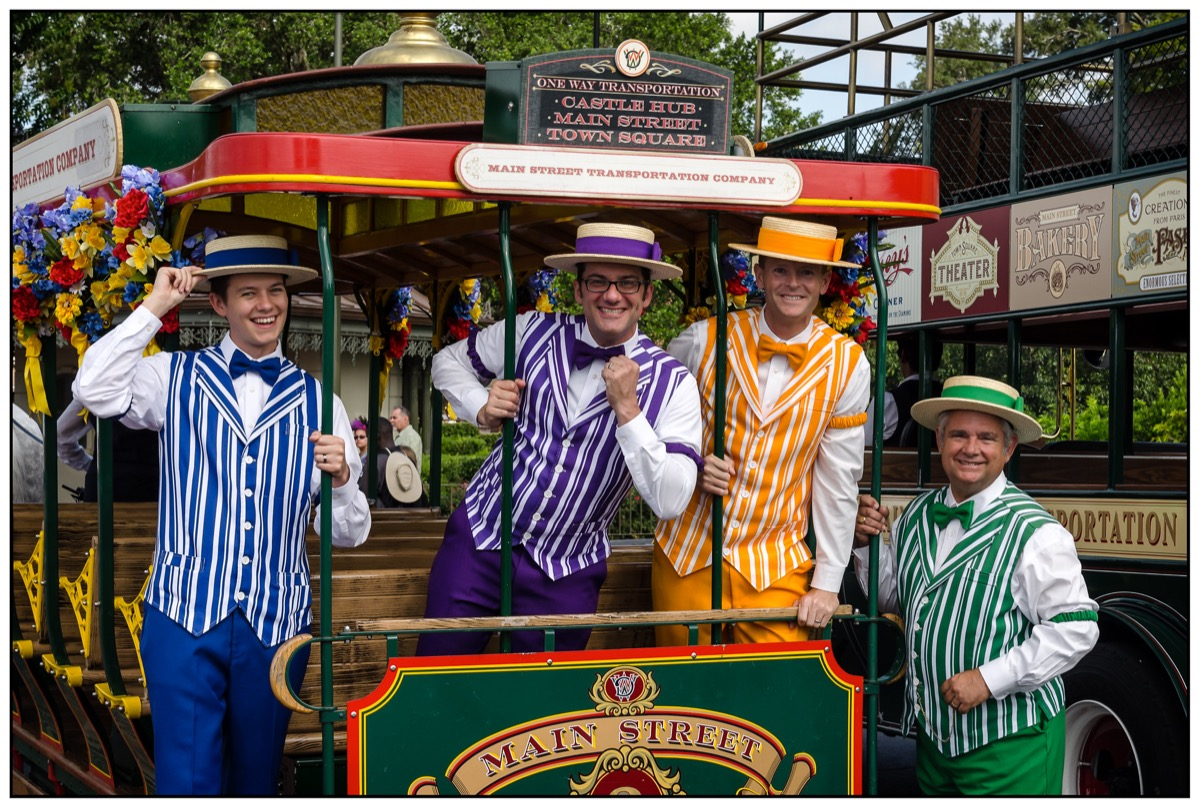four men in retro dresses on a trolley during a dapper day in disneyland