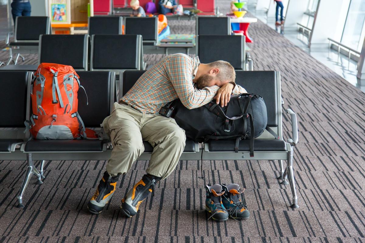 man sleeping at the boarding gate