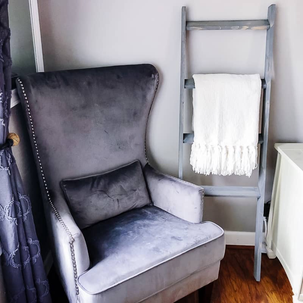 gray chair next to ladder with blanket on it