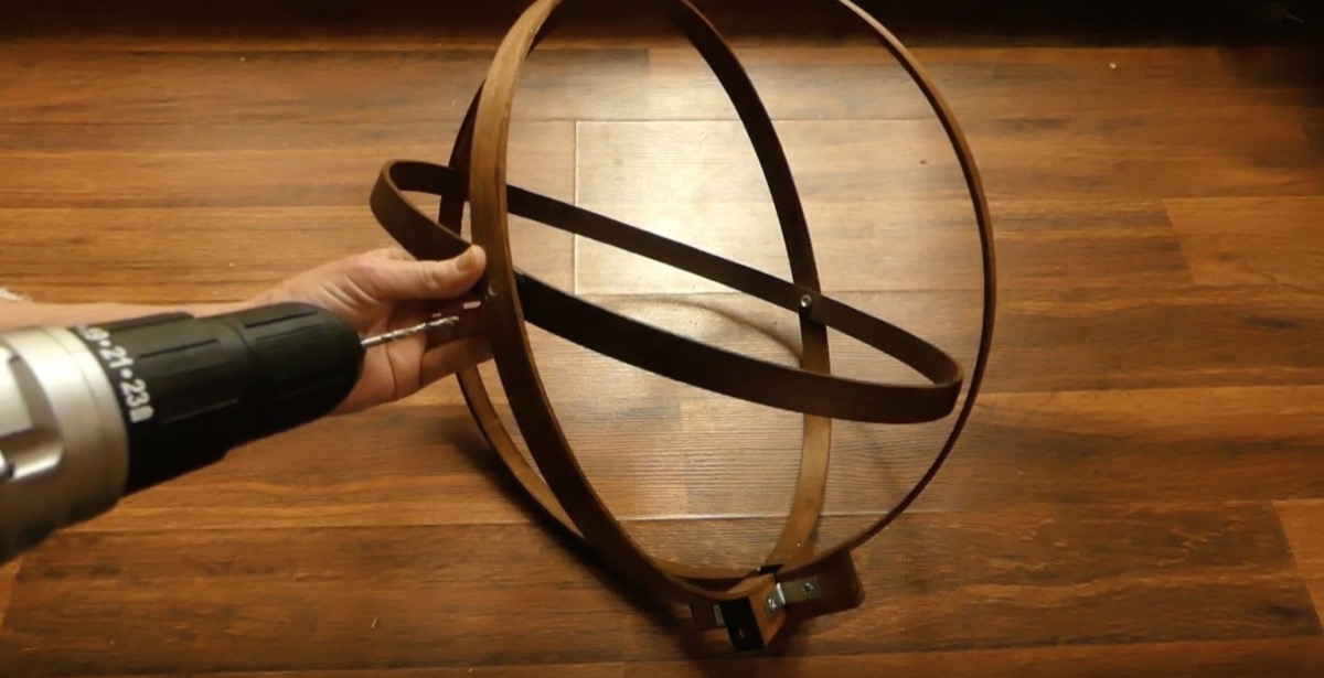 white hand and drill making pendant light hoop
