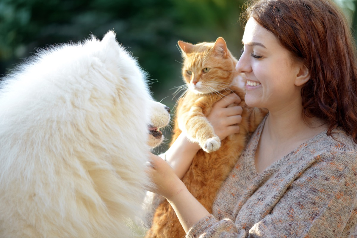 Woman holding her cat and hanging out with her fluffy dog