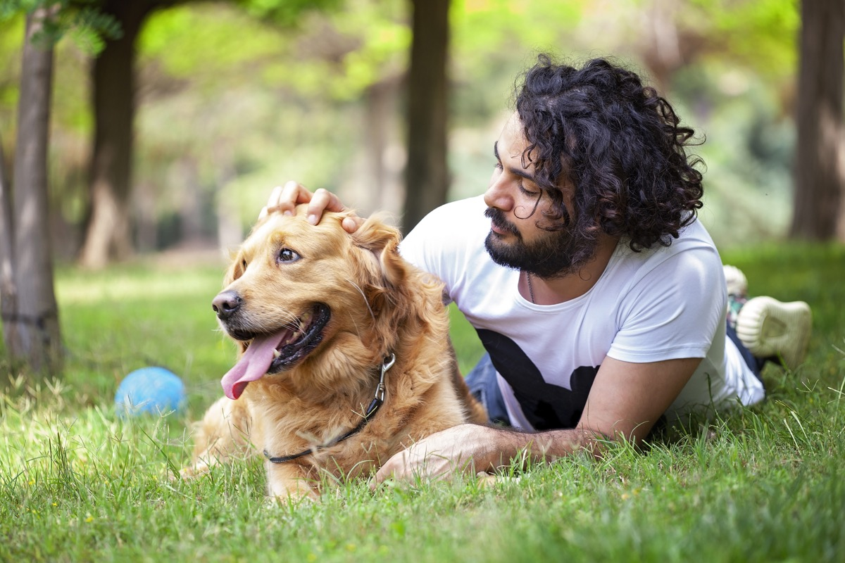 young man spending time with his Golden Retriever outdoors.