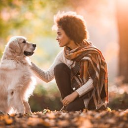 Happy African American woman speaking to her dog at the park.