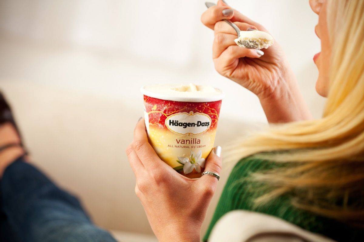 Woman eating vanilla ice cream straight from the container