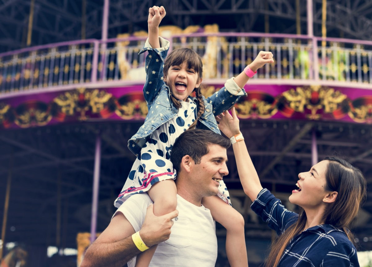 a family with a young daughter at an amusement park
