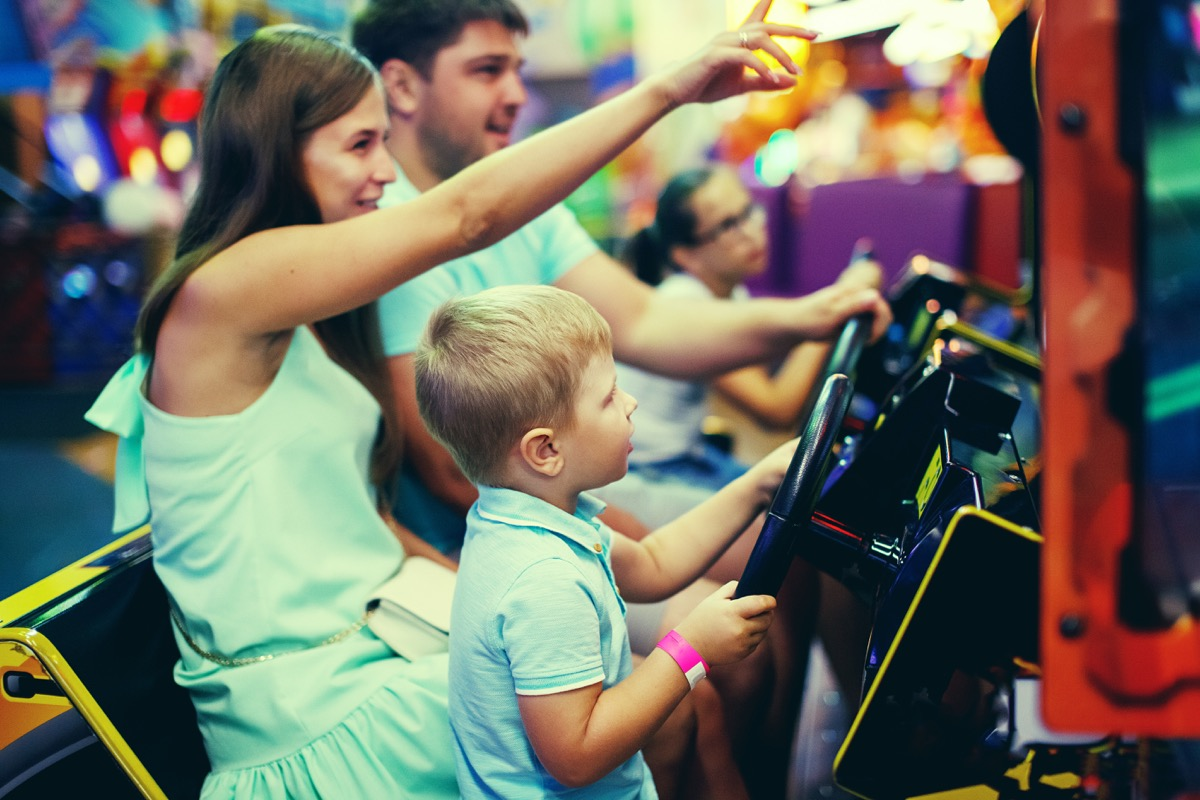Family playing a driving game at an arcade
