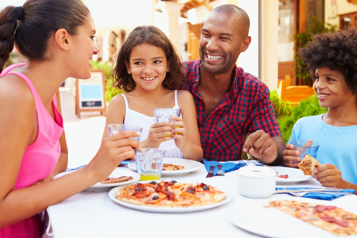 a family of four sits around an outdoor table at a restaurant