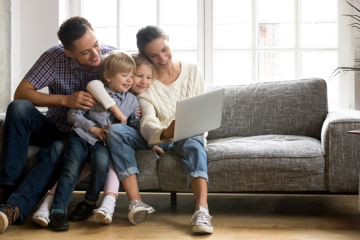 Family looking at the computer together smiling on the couch