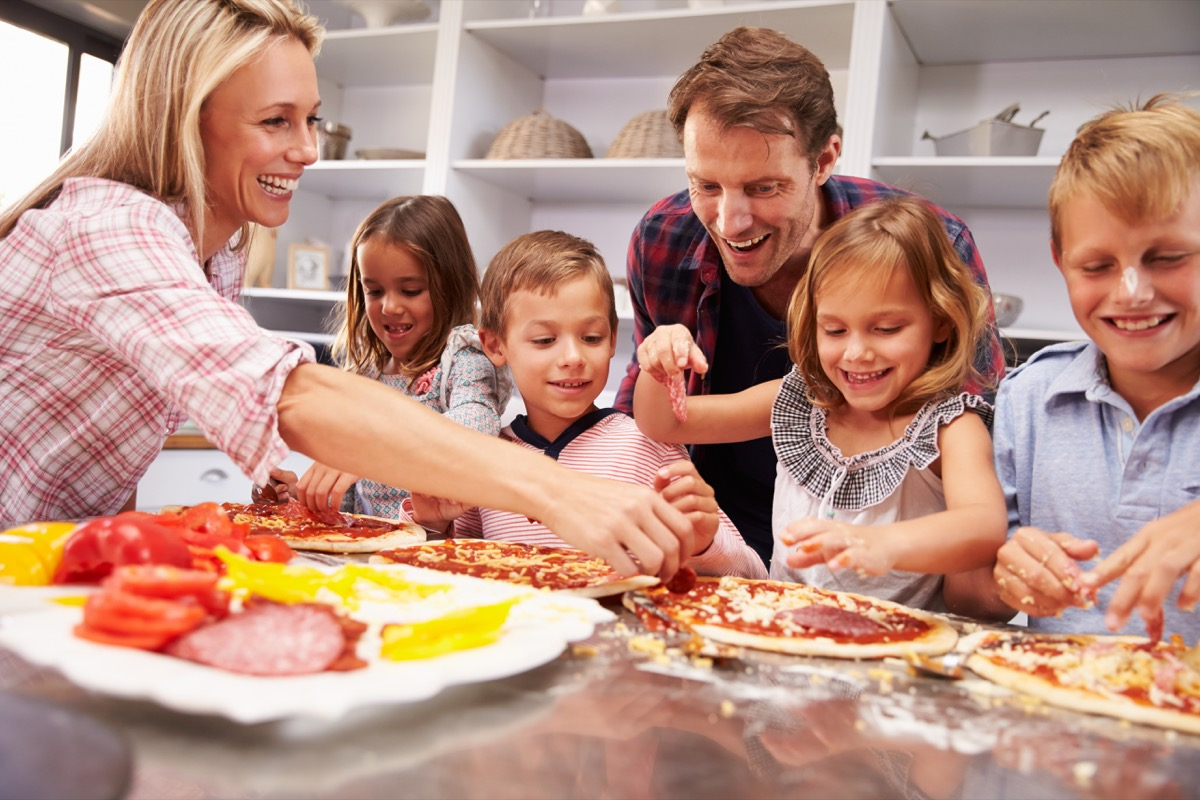 Family making a homemade pizza