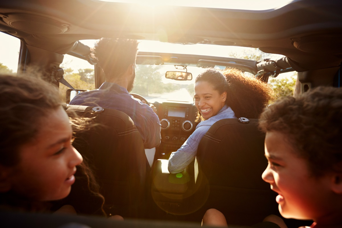 Family taking a road trip in their sun drenched car