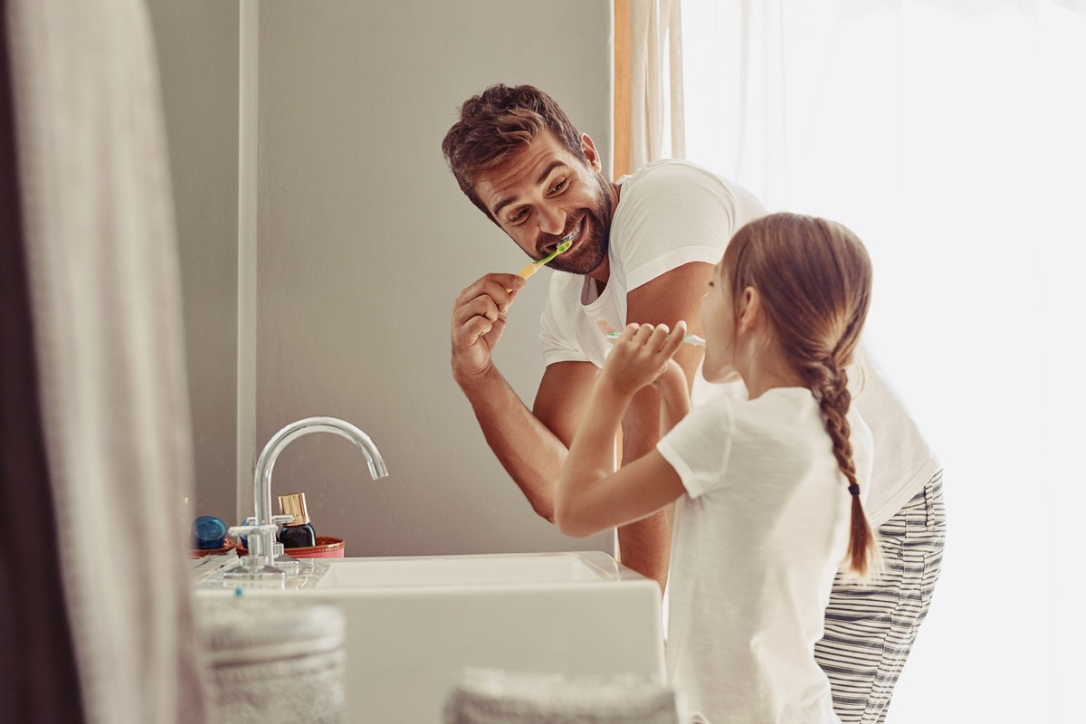 Happy father and his little girl brushing their teeth together in the bathroom