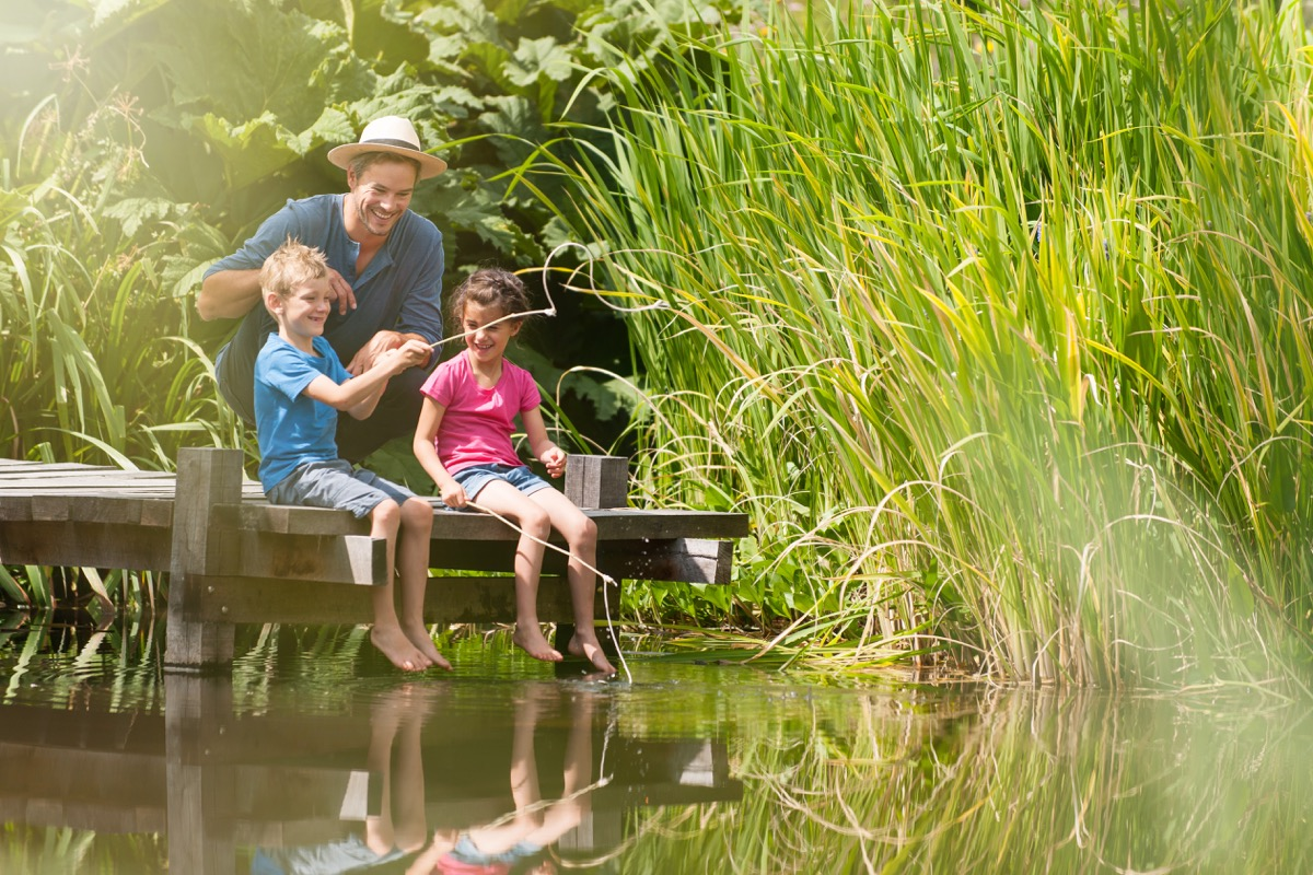 Father and children fishing on a lake