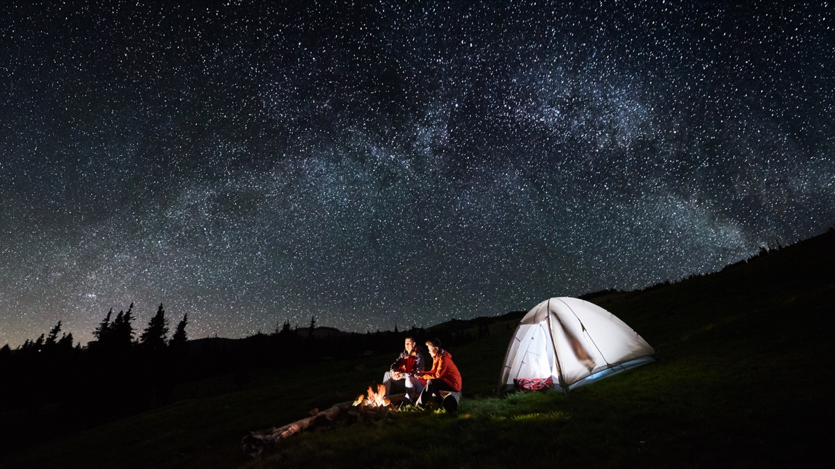 Father and son sitting by a fire camping with a tent sleeping under the stars