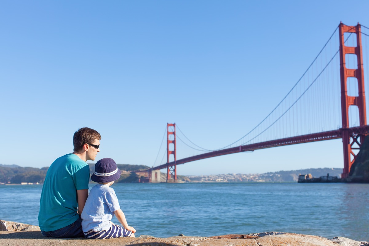 Father and son sitting and looking at the Golden Gate Bridge
