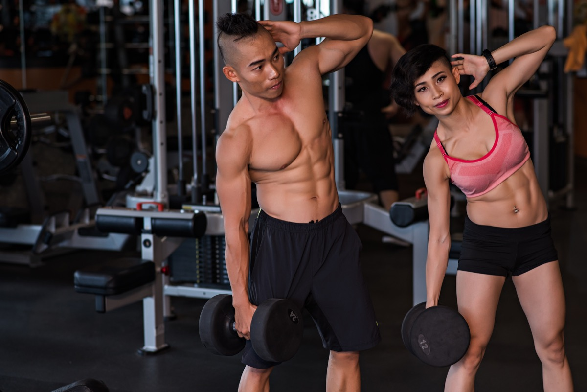 Fit couple doing dumbbell side bends at the gym