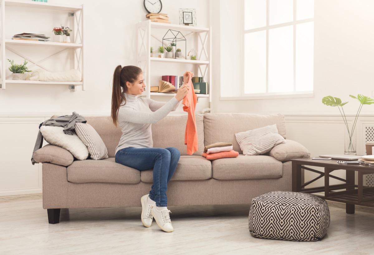 Girl folding laundry on couch