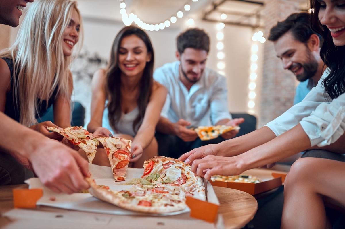 Friends hanging out and eating pizza with a lot of toppings together