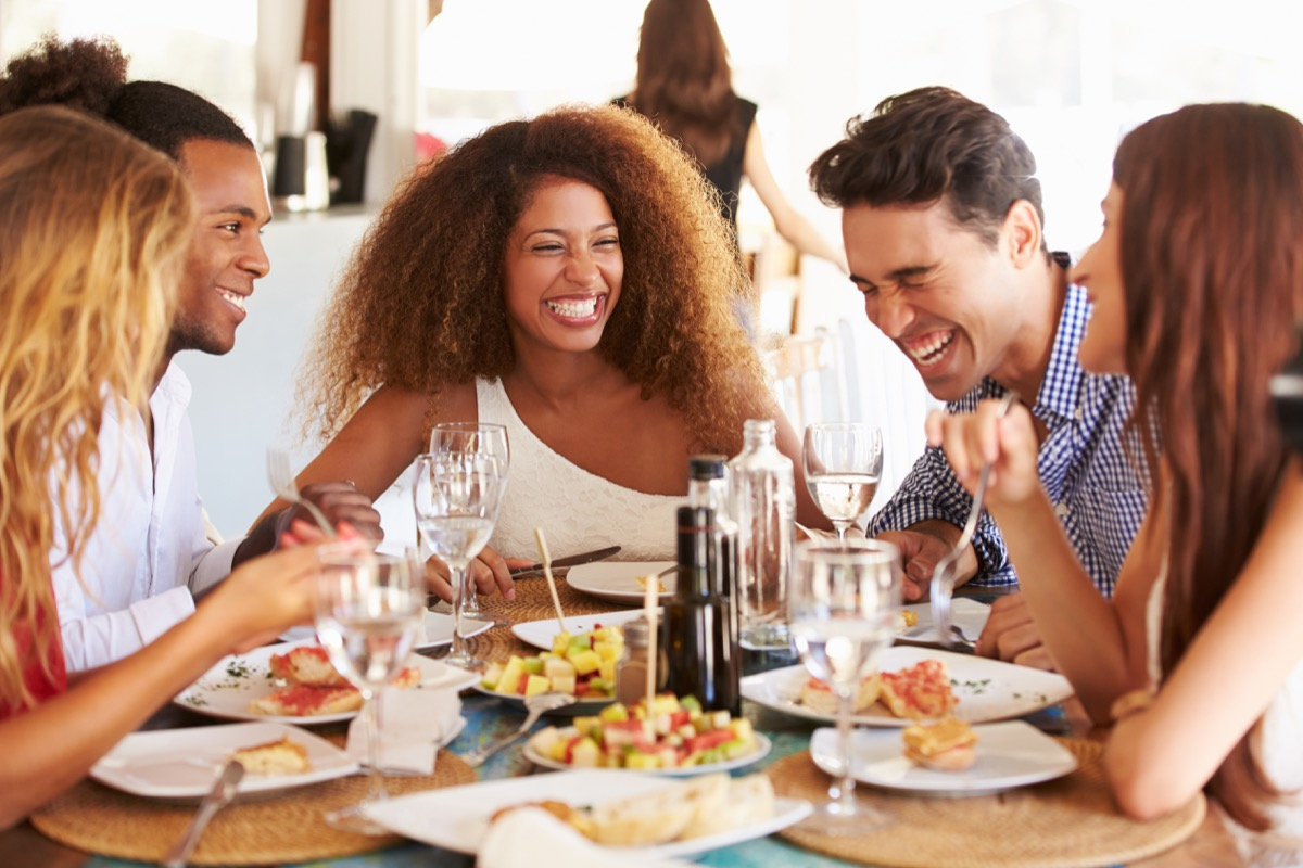 Group of multicultural friends laughing and enjoying a meal