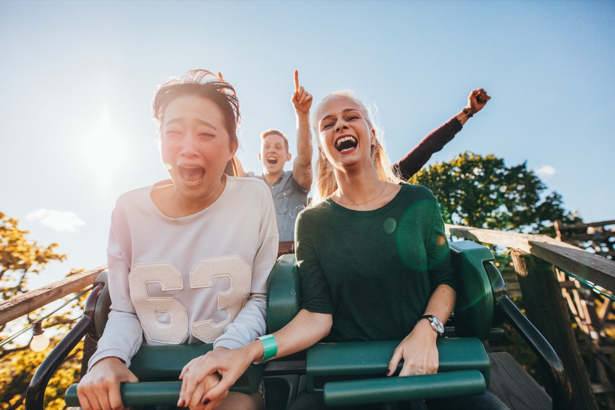 Friends on a rollercoaster one scared and screaming another excited laughing