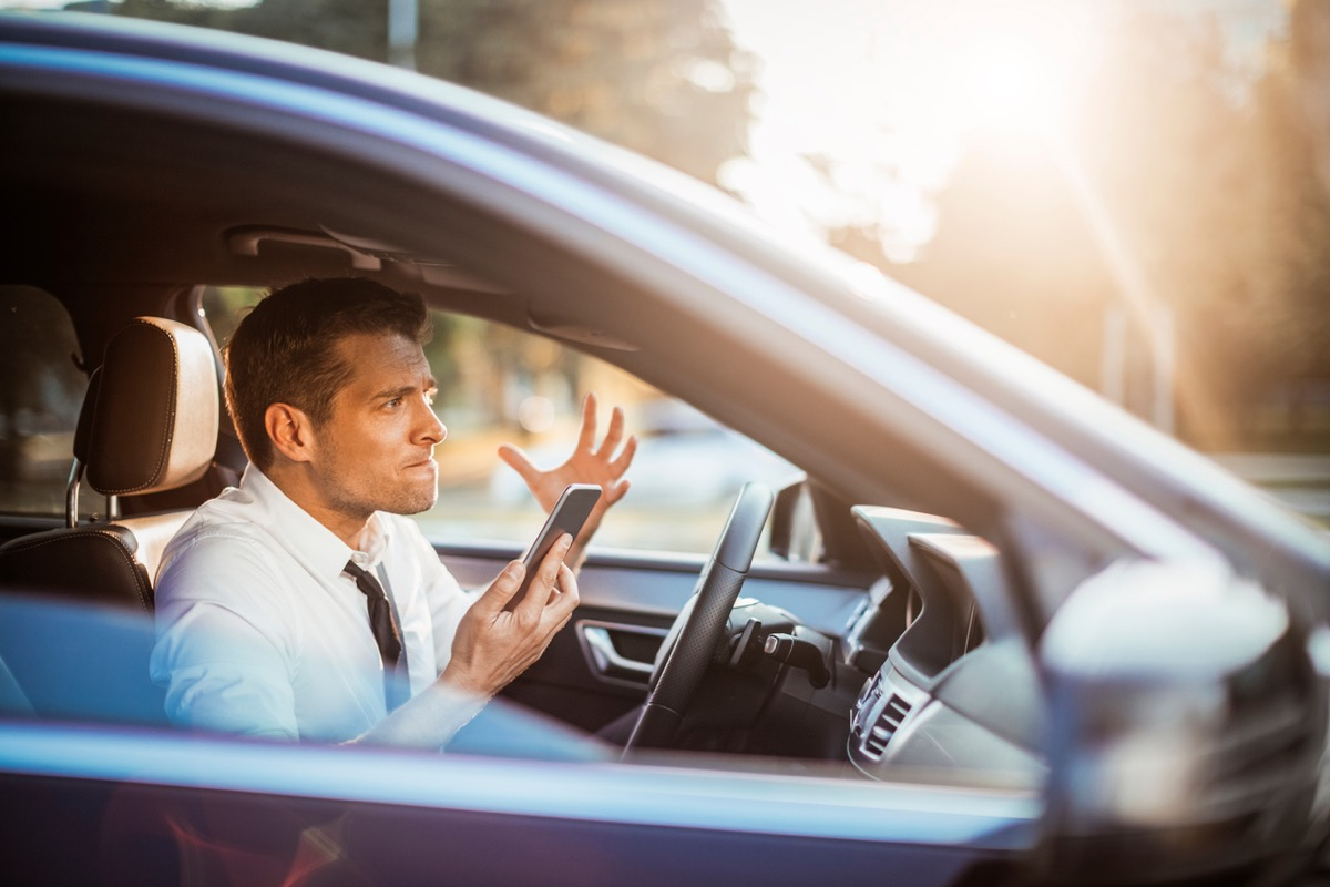 Close up photo of a businessman yelling at his phone while driving