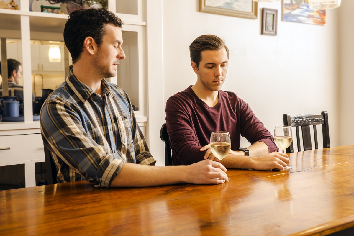 male gay couple sitting at a dining table with serious looks on their faces.. Real people. Real couple.