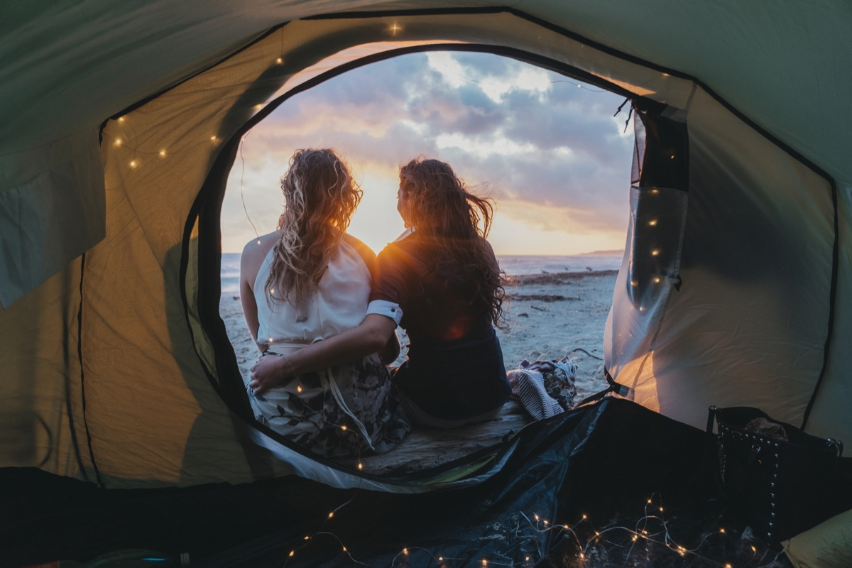 Young adult lesbian couple admiring the sunset in a tent on the beach on vacation