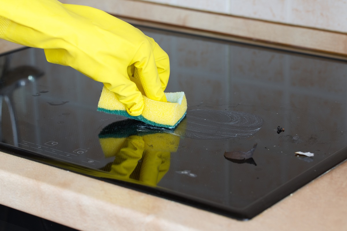 gloved hand scrubbing cooktop