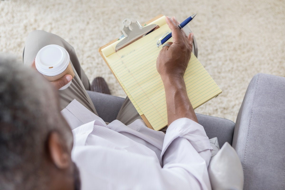 Unrecognizable senior man holds a notepad. He is making a 'to do' list. He is sitting in a chair in his living room and is holding a cup of coffee.