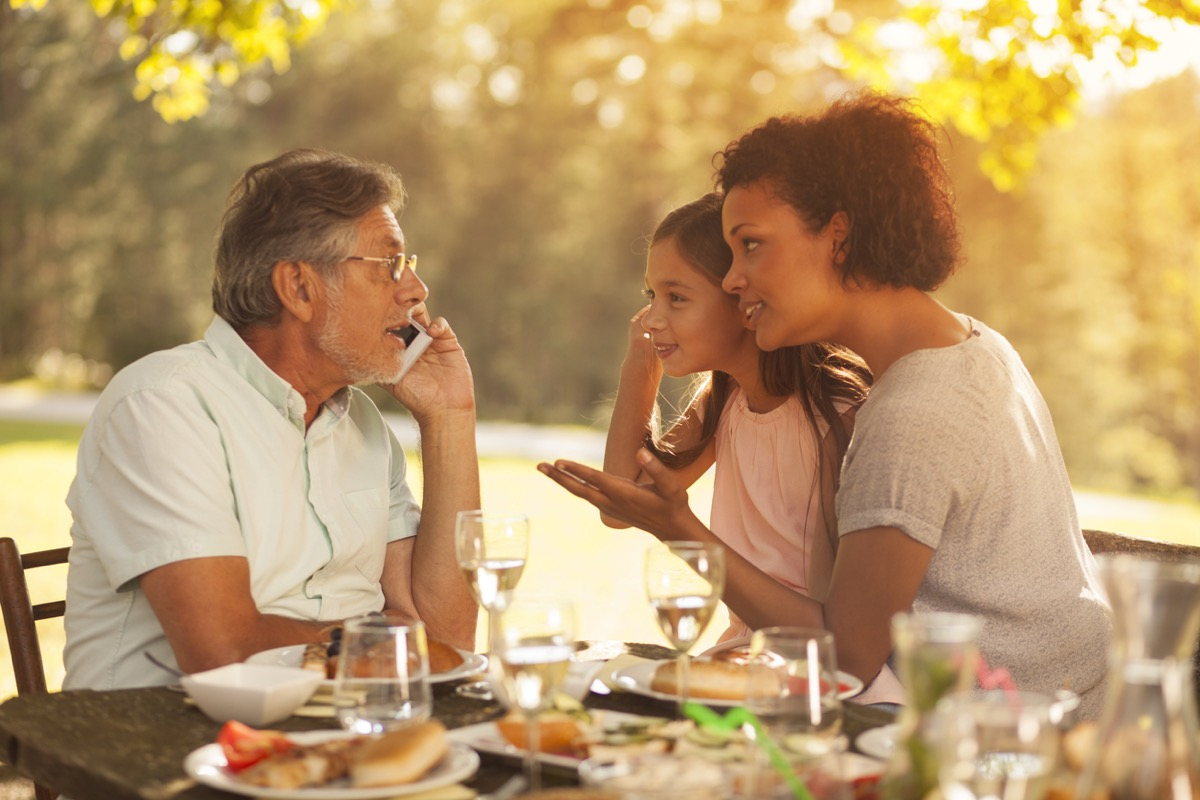 Senior man, his granddaughter and her mother on a family picnic