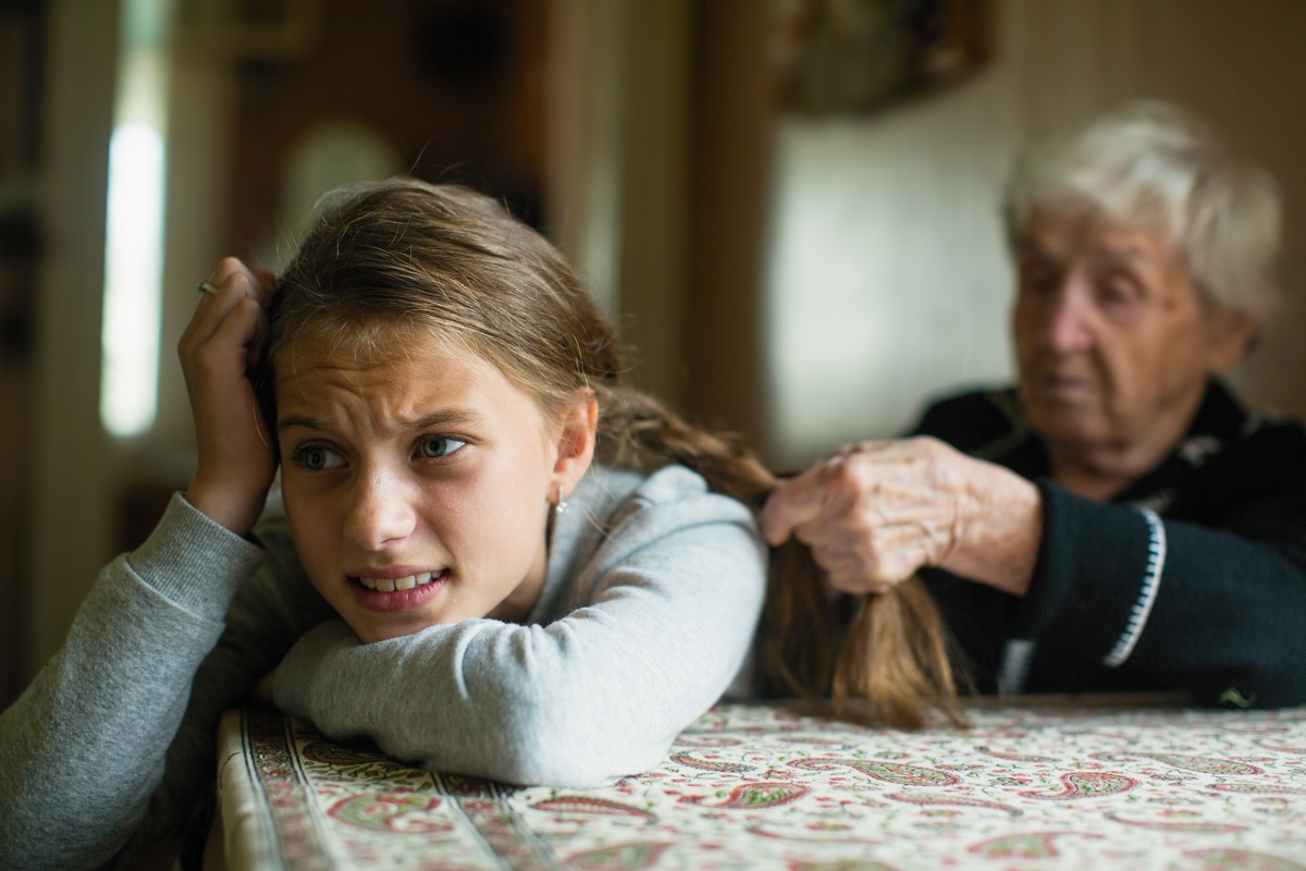 upset girl having hair braided by her grandmother