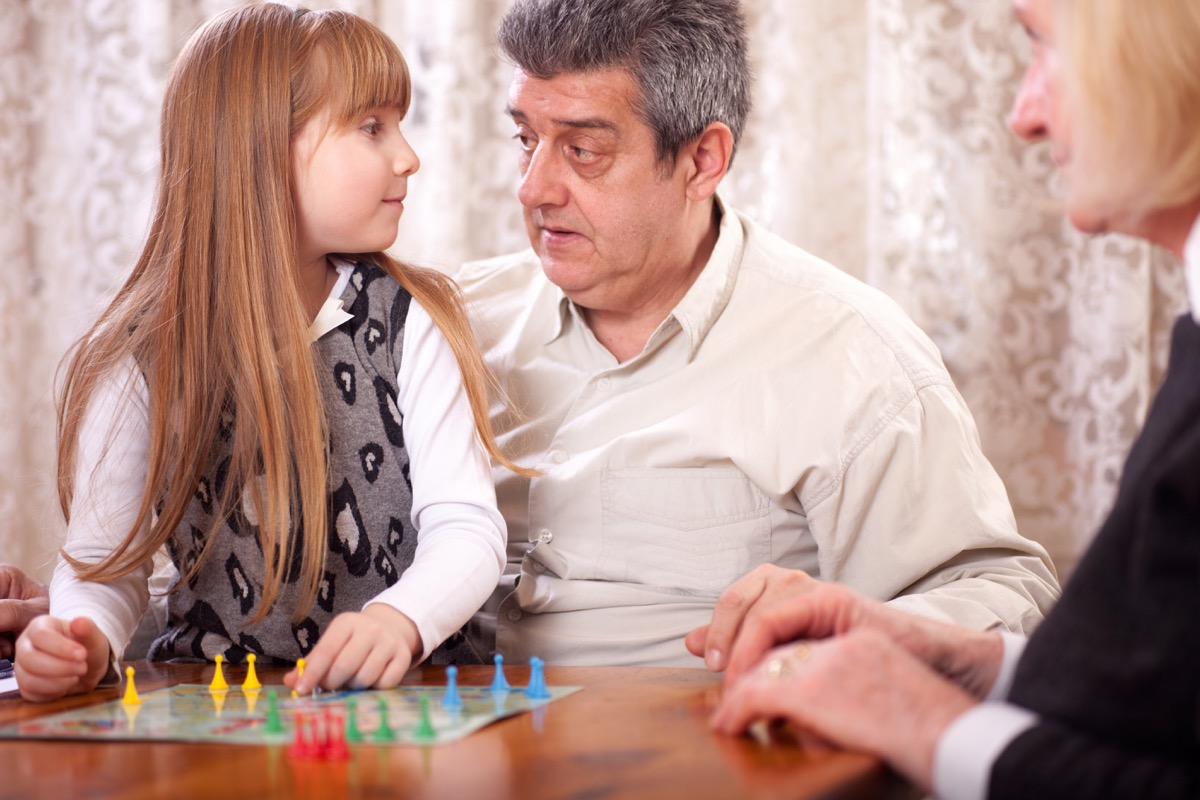 grandparents playing board game with granddaughter