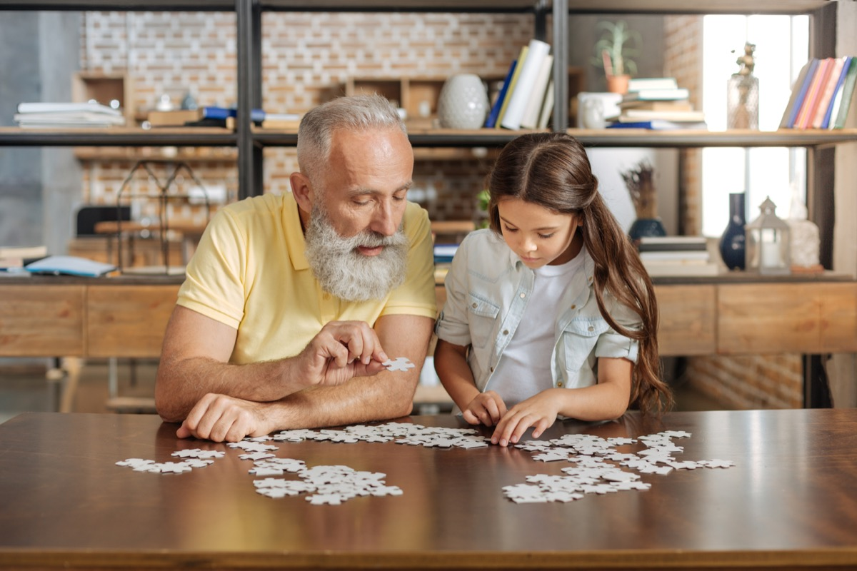 Grandfather and granddaughter doing a jigsaw puzzle together at the table