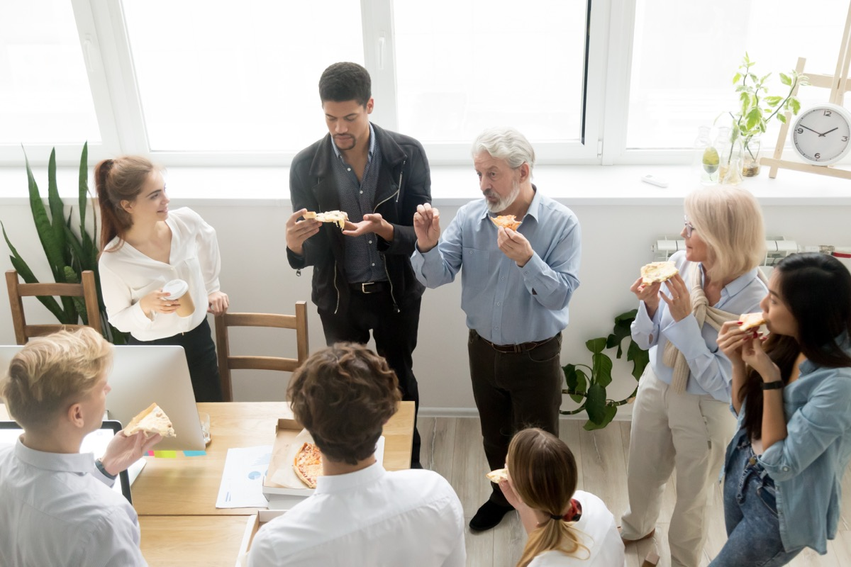 men and women standing and eating pizza in office