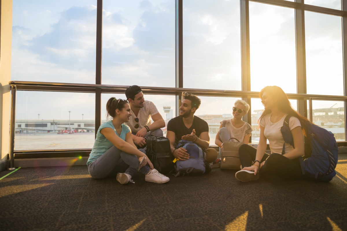 group of young adults sitting in airport