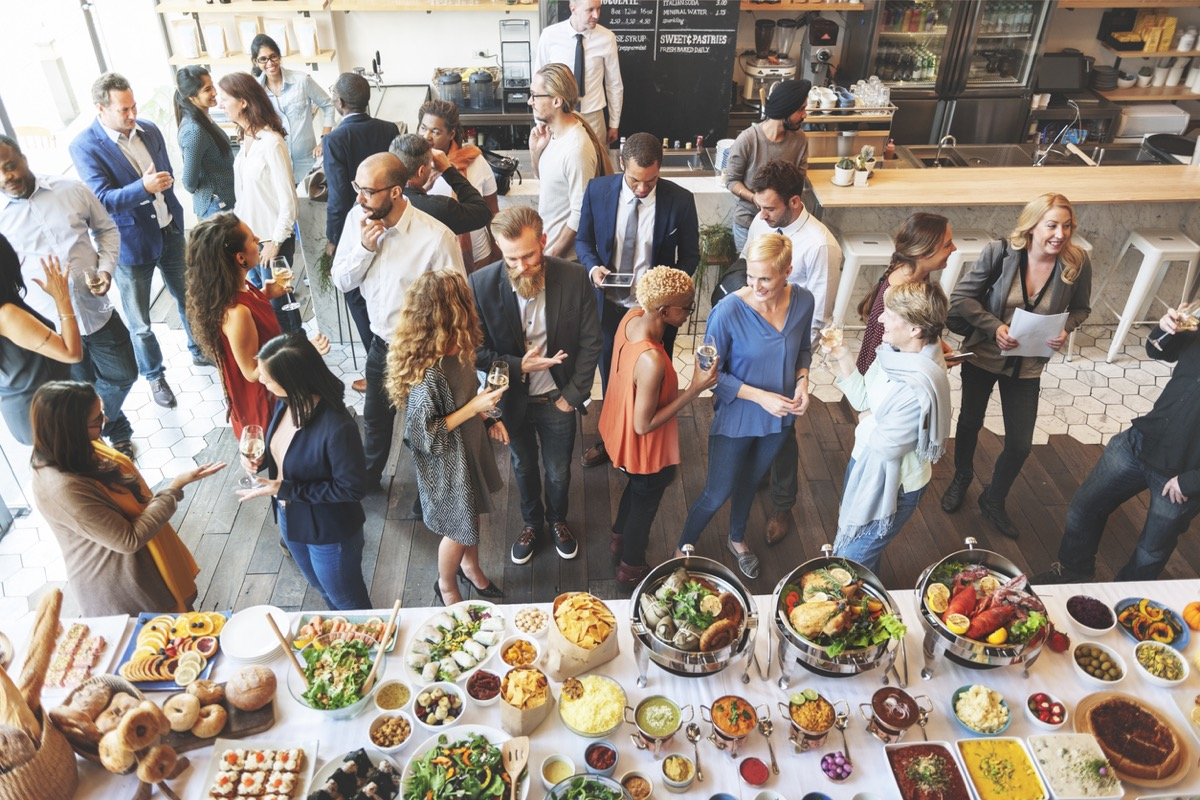 group of people standing near buffet at party