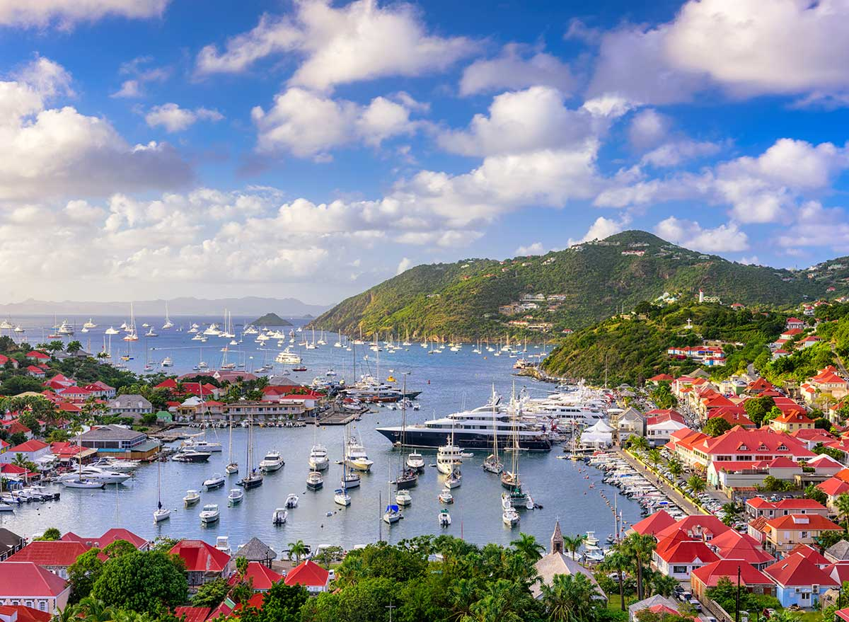 a view of the harbor, boats, and mountains of st. barts