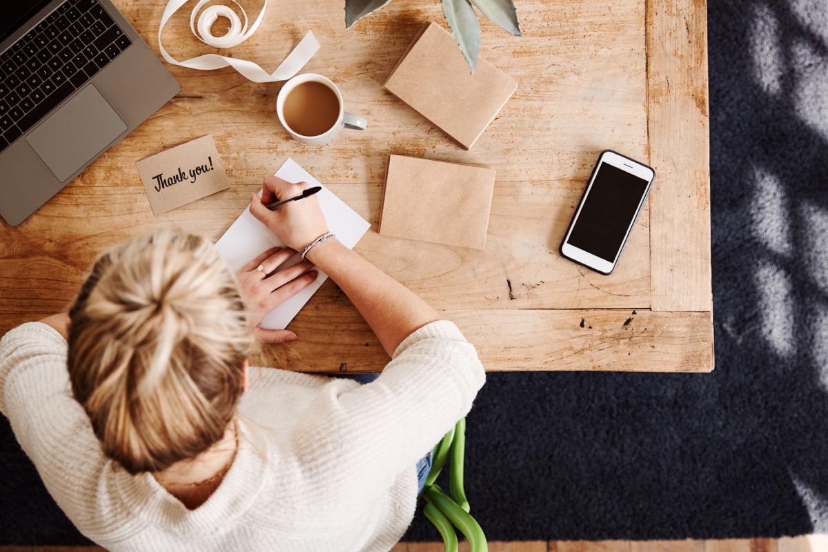 Woman writing a handwritten thank you letter