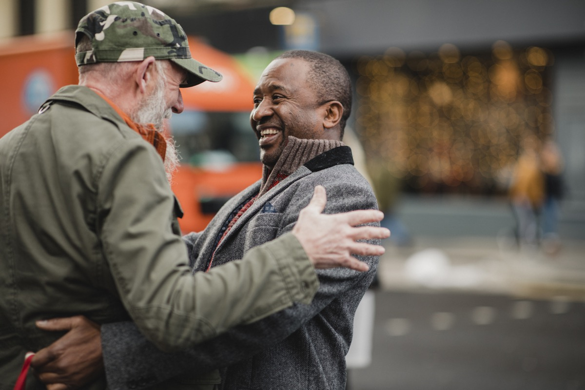 Two senior men have bumped into each other in the city and are greeting each other with a friendly hug.