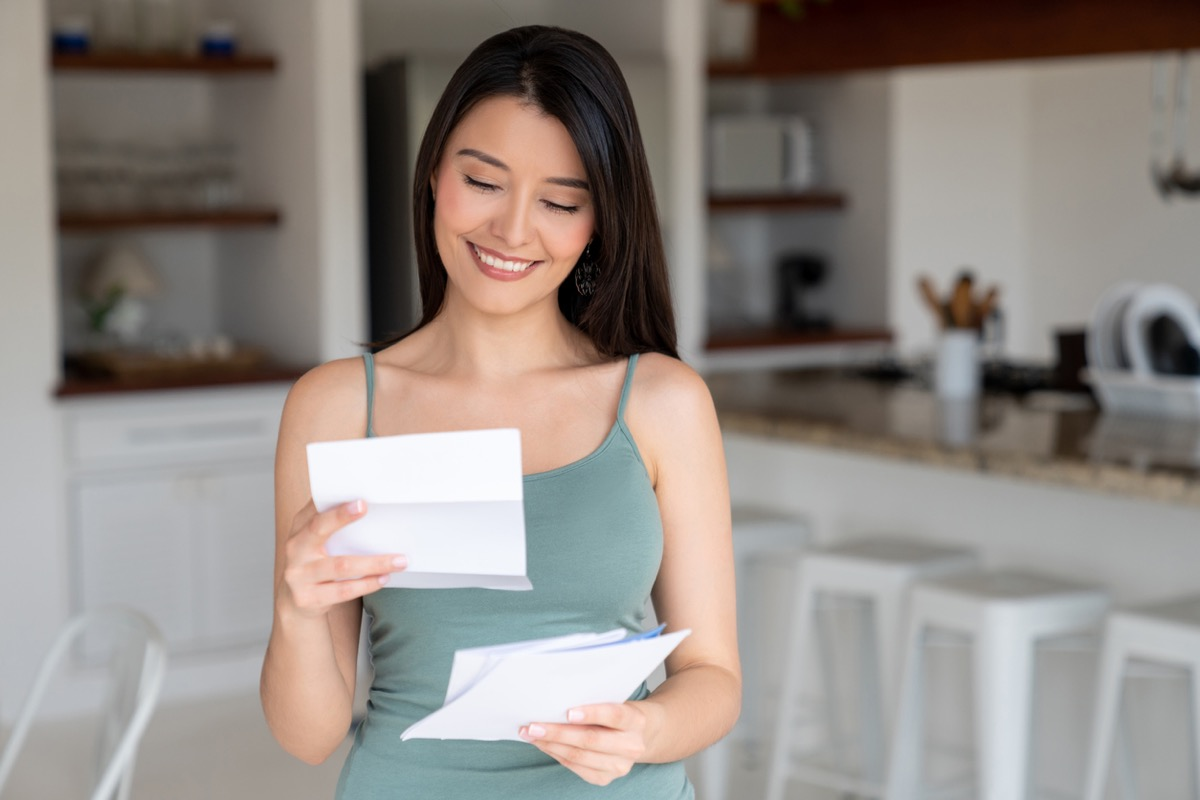 happy young hispanic woman reading letter