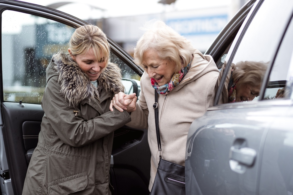 A mature woman helps a senior woman out of a car