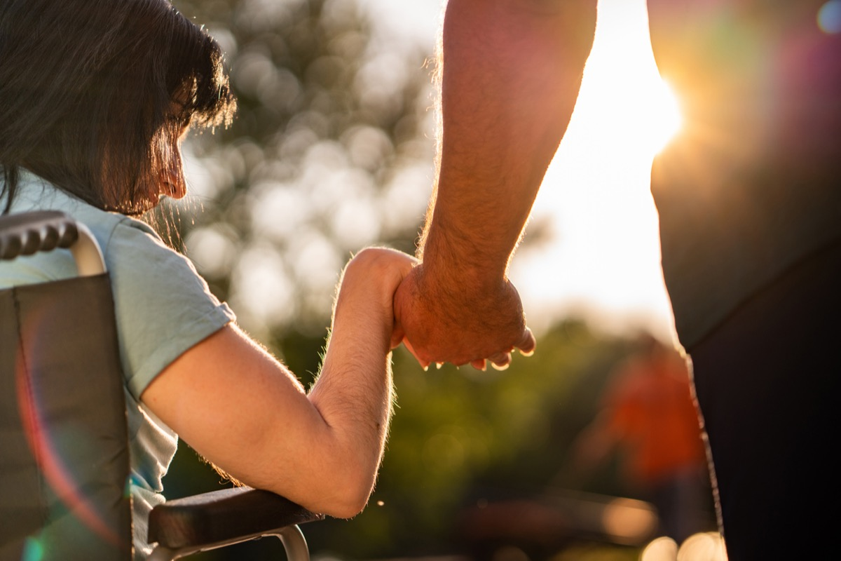 Close up of a woman in a wheelchair holding a man's hand